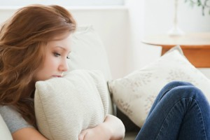 Teenage girl hugging pillow, unhappy-1559174